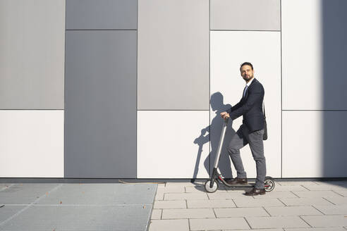 Businessman riding on electric scooter against wall in city - HMEF01161