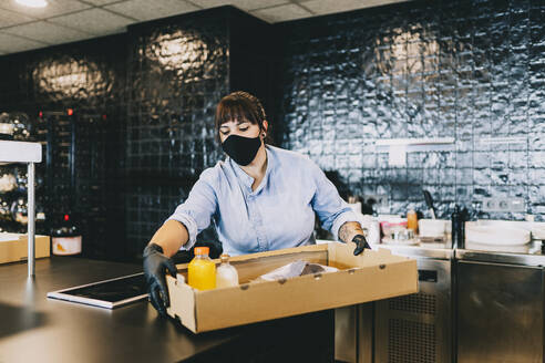 Female chef carrying cardboard box at counter in restaurant kitchen - DGOF01669