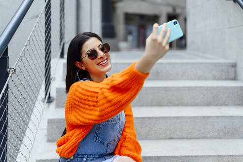 Smiling woman taking selfie through mobile phone while sitting on staircase - PGF00222