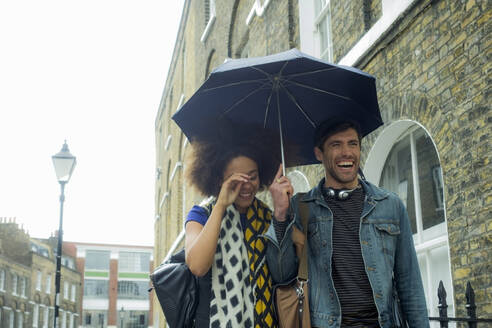 Cheerful couple with umbrella walking at city - AJOF00610