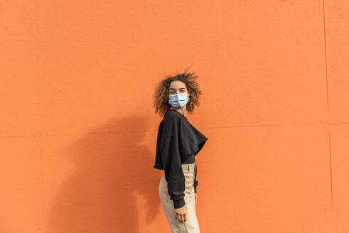 Young woman wearing face mask looking away while standing against orange wall - MEF00002