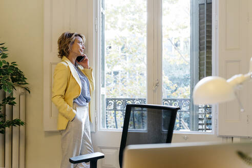 Female entrepreneur talking on smart phone while looking through window standing in office - JRFF04939