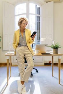 Businesswoman using smart phone while leaning on table while standing in office - JRFF04942