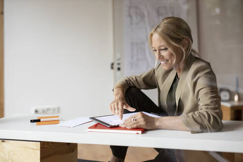 Smiling businesswoman using digital tablet while sitting at home - PESF02166