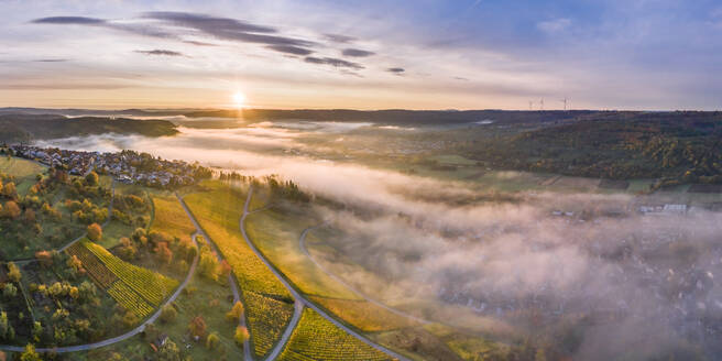 Germany, Baden Wurttemberg, Remstal, Drone view of countryside town at foggy sunrise - STSF02660