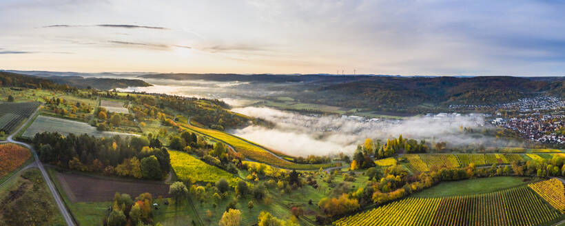 Germany, Baden Wurttemberg, Remstal, Drone view of countryside town at foggy sunrise - STSF02666