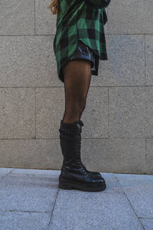 Young woman wearing boots standing on footpath by wall - RSGF00435