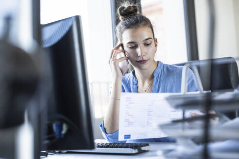 Young businesswoman holding paper while talking on mobile phone at office - UUF22076