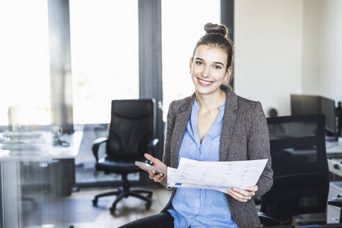 Smiling businesswoman with paper using mobile phone while standing at office - UUF22088