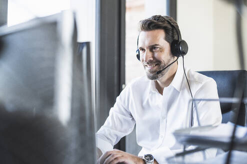 Businessman wearing headphones using computer while sitting at office - UUF22097