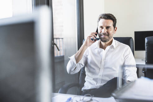 Mature businessman talking on mobile phone while sitting on chair at office - UUF22100