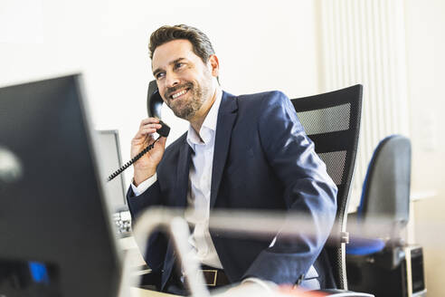 Smiling businessman talking on telephone while sitting on chair at office - UUF22124