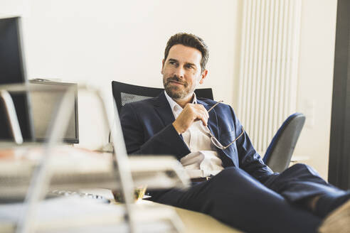 Thoughtful businessman looking away while sitting at office - UUF22136
