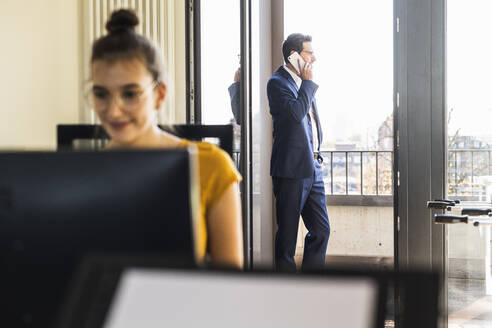 Colleague working on computer while sitting in office with businessman standing in background by balcony - UUF22145