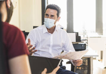 Business people wearing face mask having discussion in meeting while sitting at office - UUF22157