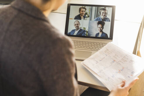 Businesswoman holding document while attending video conference on laptop at office - UUF22160