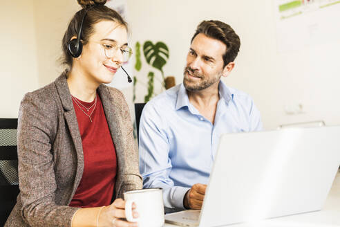 Smiling businesswoman wearing headphones drinking coffee while working with colleague on laptop at office - UUF22163