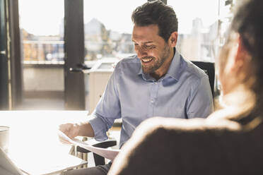 Smiling businessman analyzing document while working with colleague at office - UUF22172
