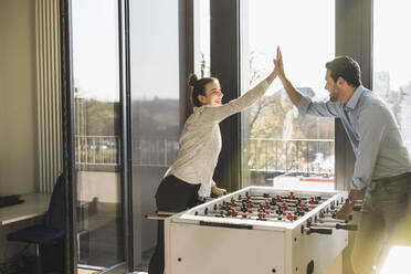 Cheerful business people giving high-five while playing Foosball at office - UUF22184