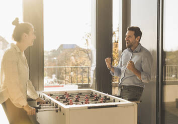 Businessman screaming while playing Foosball with colleague at office - UUF22187