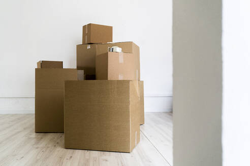 Brown cardboard boxes against wall in living room of new house - GIOF09685