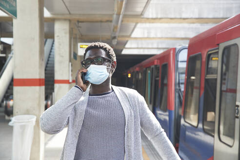 Male entrepreneur wearing protective face mask while talking on mobile phone at railroad station - PMF01562