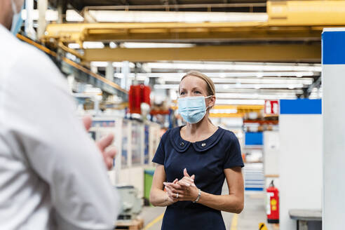 Female entrepreneur discussing with male colleague while standing in factory during pandemic - DIGF13271