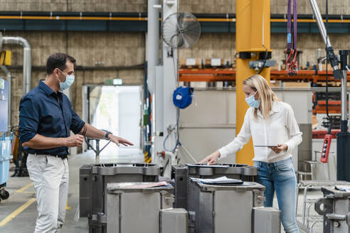 Female entrepreneur and male colleague analyzing machinery while standing in factory during pandemic - DIGF13319