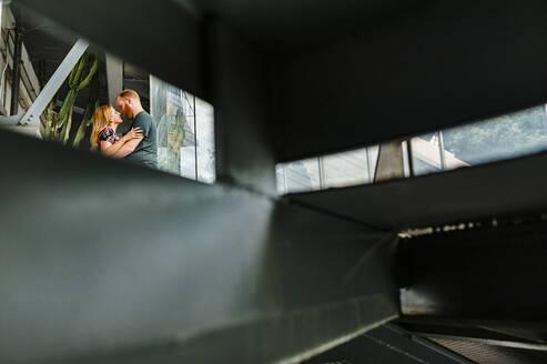 Heterosexual couple embracing each other seen through window - JMPF00647