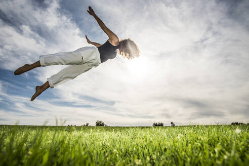 Young female athlete doing acrobatic activity in park against cloudy sky - ABAYF00029