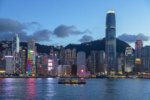 Star Ferry in Victoria Harbour and skyline of Hong Kong Island at dusk, Hong Kong, China, Asia - RHPLF18245