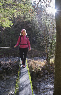 Senior woman hiking alone in forest - MRF02378