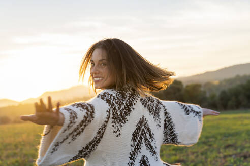 Cheerful young woman dancing with arms outstretched during sunset - AFVF07610