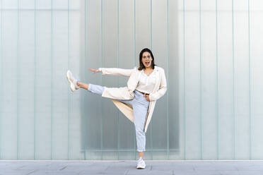 Cheerful businesswoman with stretching leg and arm while standing against glass wall - AFVF07639