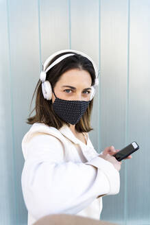 Female entrepreneur holding smart phone against glass wall during pandemic - AFVF07648