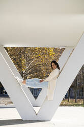 Smiling businesswoman relaxing on column in park - AFVF07651