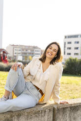 Smiling Businesswoman sitting in garden on sunny day - AFVF07693