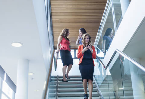 Female coworkers moving down steps in office - AJOF00635