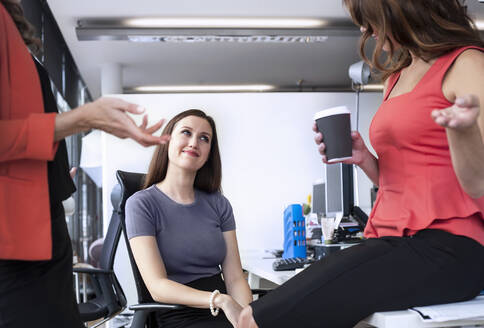 Female coworkers planning strategy in meeting at office - AJOF00647