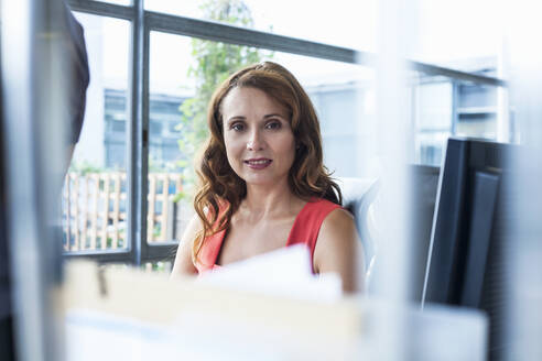 Businesswoman sitting in office - AJOF00650