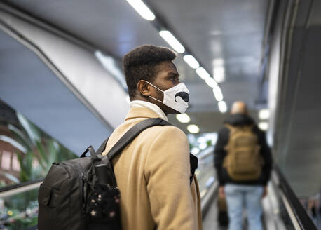 Young man wearing face mask standing on escalator at station - JCCMF00015