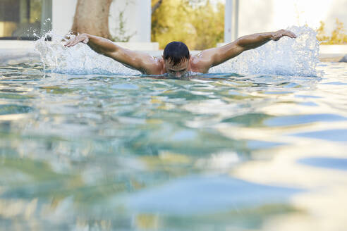 Young man doing butterfly stroke in swimming pool - UKOF00083