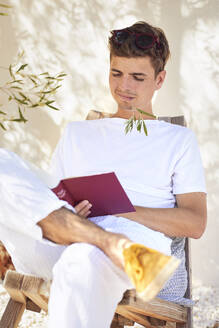Young man with stem in mouth reading book against wall - UKOF00098