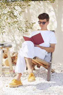 Young man sitting on chair while reading book against wall in backyard - UKOF00101