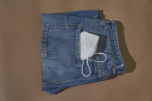 From above of folded jeans with white protective mask in pocket placed on brown background. - CAVF90725