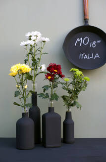 Cast iron frying pan and black bottles with chrysanthemums - GISF00697