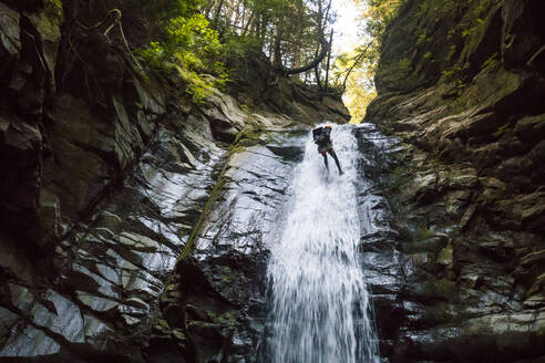 Low angle view of explorer rappelling down waterfall - CAVF90865