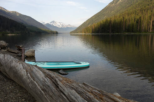 SUP board on shore of lake on background of mountain ridge in morning - CAVF90874