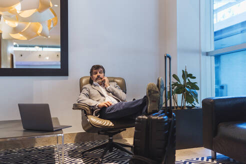 Businessman talking on phone while relaxing in waiting room at hotel - DGOF01773