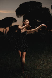 Elegant female ballet dancer in dress standing in meadow with raised arms and performing in dark park in Iceland - ADSF17776